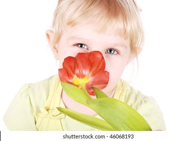 Little blond girl sniffing tulip portrait