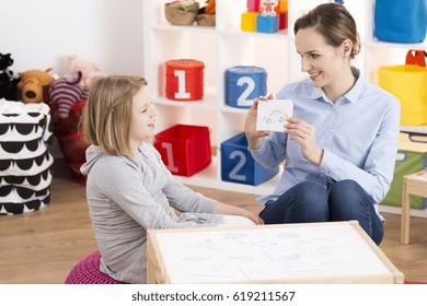 Little blond girl visiting professional speech therapist