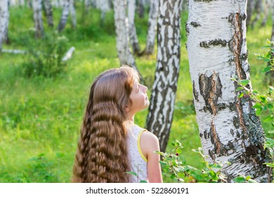 Little blond girl with wavy hair in the forest.