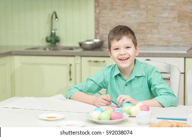 Little blond kid boy coloring eggs for Easter holiday in domestic kitchen