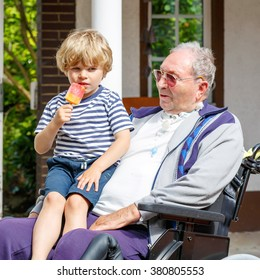 Little blond kid boy and grandfather on wheelchair eating together ice cream in summer.