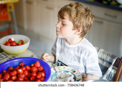 Little blond kid boy helping and making strawberry jam in summer. Funny child cleaning berries and preparing for cooking jam. Kid eating ripe strawberries in domestic kitchen.