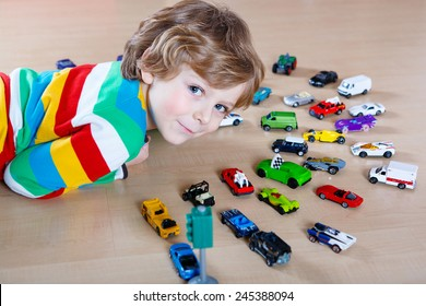 Little blond kid boy playing with lots of toy cars indoor. Toddler wearing colorful shirt and having fun.