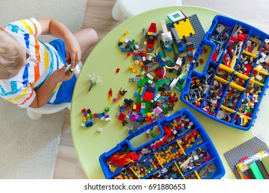 Little blond kid boy playing with lots of colorful plastic blocks indoor. Blocks of lego are sorted. Storage of lego classic.