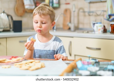 Little blond kid tries freshly baked shortbread, sitting at the kitchen table. Grimacing face.