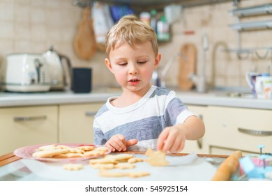 Little blond kid tries freshly baked shortbread, sitting at the kitchen table. Concentrated face expression.