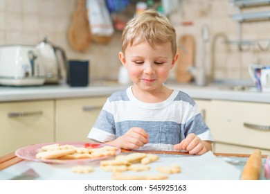 Little blond kid tries freshly baked shortbread, sitting at the kitchen table. Smiling face.
