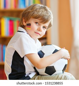 Little blond preschool kid boy with ball watching soccer football cup game on tv. Funny happy crying child fan having fun and cheering winning football team. Champions and world cup concept