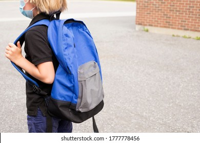 Little blond schoolboy wearing mask during corona virus and flu outbreak. School kid cough. Little kid wears blue backpack,breathes through mask, going to school.Back to school concept after reopening