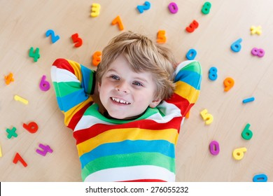Little blond toddler child playing with lots of colorful plastic digits or numbers, indoor. Kid boy wearing colorful shirt and having fun with learning math