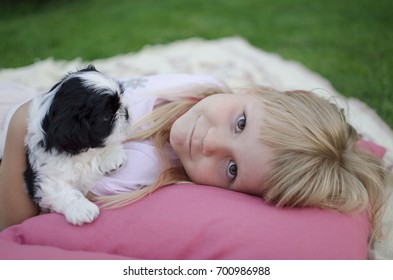 Little blond Ukrainian girl lying on the pillow with her puppy. Shih tzu pet. Smiling lady