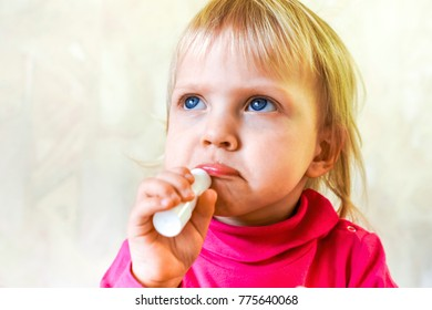 little blonde baby girl with blue eyes in pink crimson reglan try to paint herself with lipstick. small beauty painting her lips of pink lipstick. little girl as an adult women