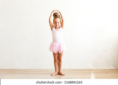 Little blonde balerina girl dancing and posing in dance club with wooden floot an white textured plaster wall. Young ballet dancer in pink tutu dress, having fun and smiling. Backgroud, copy space.