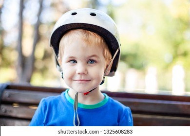 Little blonde boy 3 years old in white sport helmet and blue t-shirt outside. Special problems with kid's eyes. Myopie, astigmatism, cross-eyed.