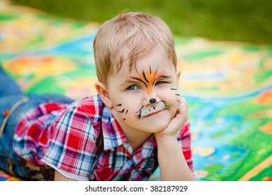 The little blonde boy with with face art on birthday party