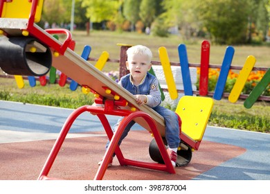 Little blonde boy playing on the playground, outdoors summer