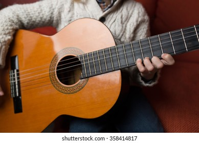 Little blonde boy playing spanish guitar at home, guitar detail.