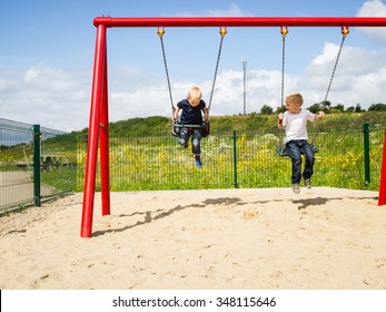 Little blonde boys brothers having fun at the playground. Children kids playing on swing outdoor. Happy active childhood.