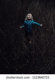 Little blonde Caucasian scared girl lost in wood forest looking up above. Child cry scream ask for help. Concept of lost  abandoned kid left alone in trouble problem.