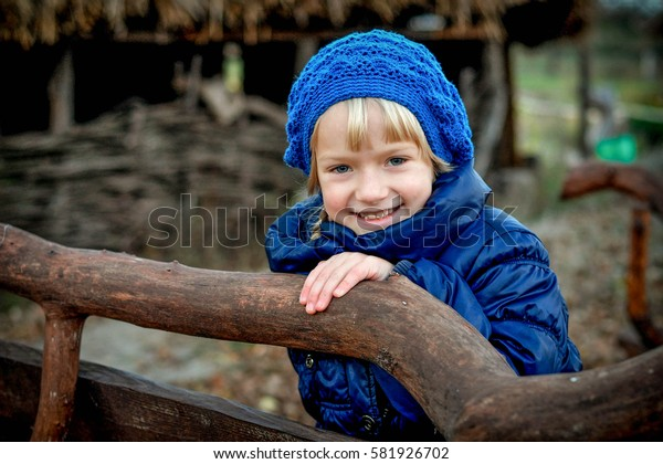 little blonde child girl smile holding wooden branch at park. wearing a blue coat and hat