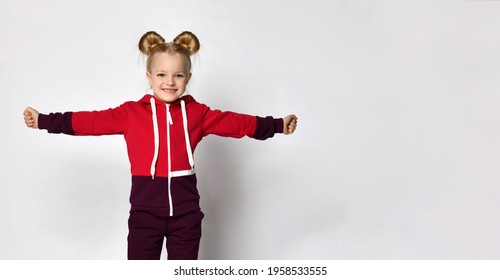 little blonde curly-haired beautiful girl in a red burgundy tracksuit stands with her arms spread wide like wings, playing an airplane or a bird on a gray wall background. Stylish casual fashion for