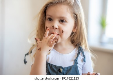 little blonde cute girl got her chocolate fingers dirty and licks them. High quality photo