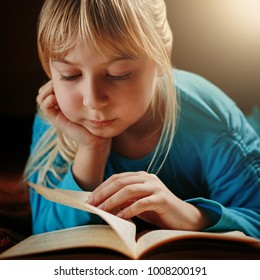 a little blonde girl in a blue blouse lies in a dark room and reads a green book.