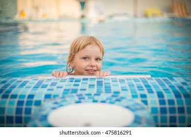 Little blonde girl in blue swimming pool outdoors