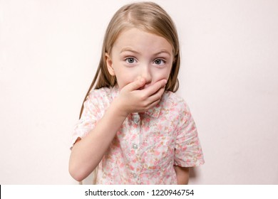 little blonde girl closes her mouth with her hand on isolated background