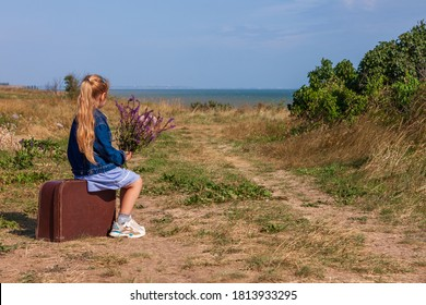 Little blonde girl in denim jacket, blue dress with vintage suitcase and flowers bouquet off-road with sea landscape. Stylish hitchhiker child with long hair on countryside trip. Kid walking outdoors.