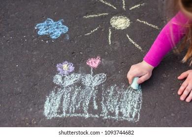 Little blonde girl is drawing a landscape onto the sidewalk