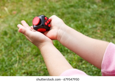 Little blonde girl holding a fidget cube stress relieving object, outdoors while playing in the middle of nature