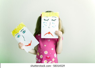Little blonde girl holding happy and sad face masks symbolizing changing emotions