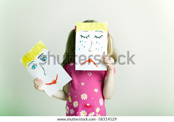 Little blonde girl holding happy and sad face masks symbolizing changing emotions