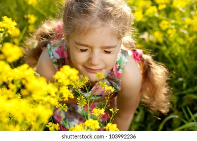 Little blonde girl inhales scent of wild flowers