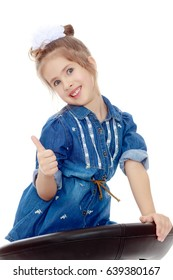 The little blonde girl with a large white bow on the head and short denim dress.She poses on a revolving chair.Isolated on white background.