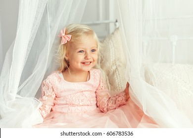 Little blonde girl laughs and plays in a beautiful gentle princess dress
