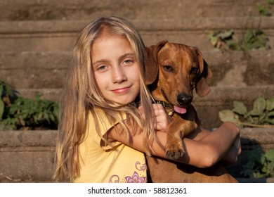 little blonde girl and a loving puppy dachshund