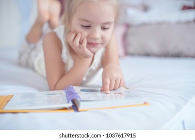 Little blonde girl lying on the bed reading a book indoors