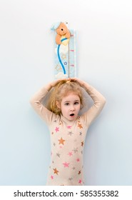 Little blonde girl measuring height against wall in room