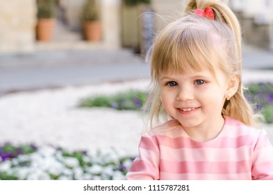 Little blonde girl in a pink dress playing on city street flowers view