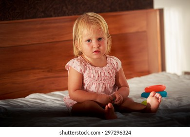 little blonde girl in pink dress sits on sofa near toys
