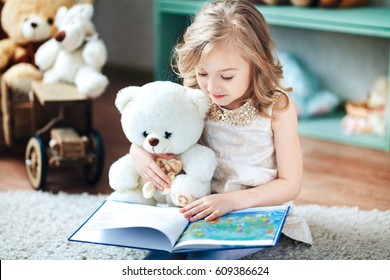 Little blonde girl is reading a book in a children's room with a toy teddy bear