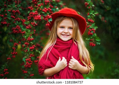 little blonde girl in a red hat, scarf in a park near a tree