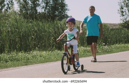 Little blonde girl riding a bicycle watched carefully by her grandfather, senior men, precious family time spent together, vintage color tones