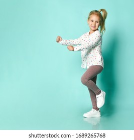 Little blonde girl in shirt with hearts print, checkered pants and white sneakers. She smiling, dancing against blue studio background. Happy childhood, fashion, advertising. Full length, copy space