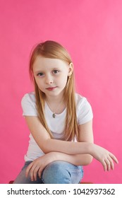 Little blonde girl sitting on pink background