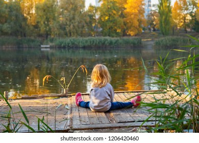 Little blonde girl sitting on a wooden pond platform and looking at water reflection. Beautiful autumn colors.