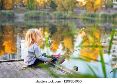 Little blonde girl sitting on a wooden pond platform and looking at water reflection with a wooden stick as a rod in her arm. Beautiful autumn colors.