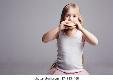 Little blonde girl in a skirt and tank top eats a big hamburger and looks at the camera on a light background.